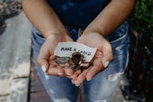 An individual is holding coins and a piece of paper that reads 'Make a change.'
