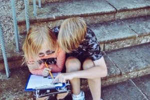 Two children are looking at a sheet of paper on a clipboard.
