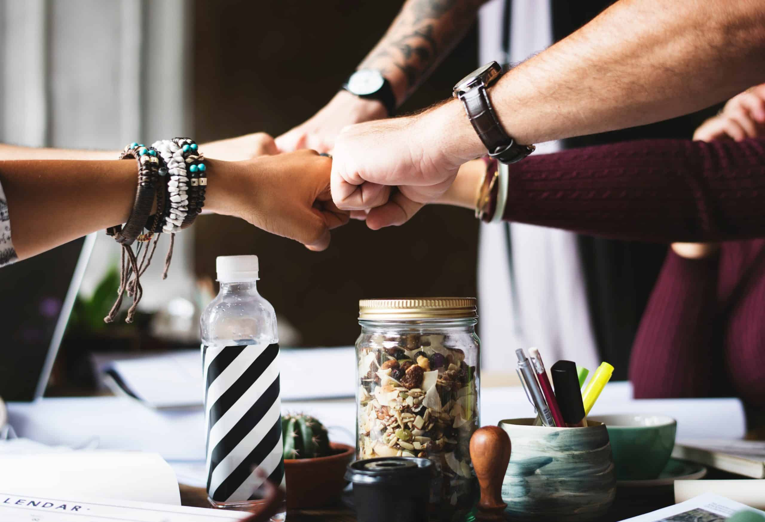A workplace team is bumping their fists together during a meeting.