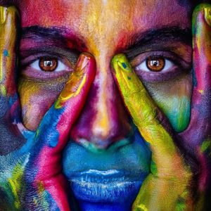 An individual is colored in a multitude of different colored paints, signifying diversity, equity, and inclusion.