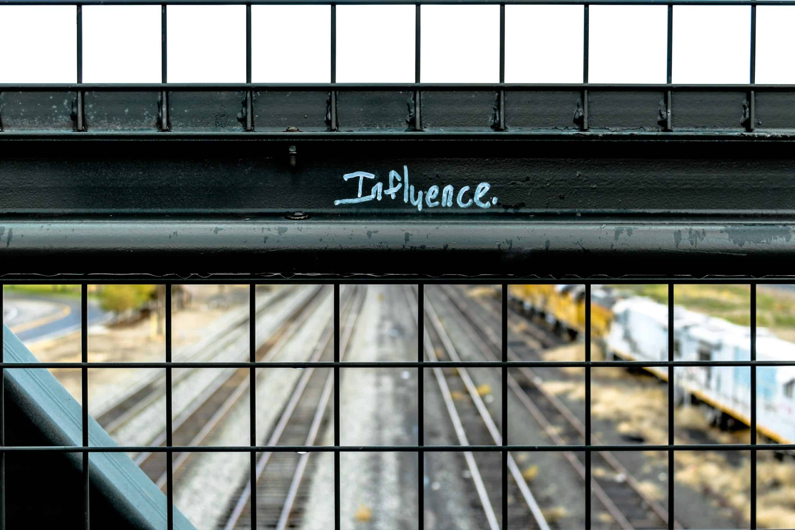 This is a photo of a metal bar for a steel wire fence on a bridge above train tracks. On the bar the word 'Influence' is written.