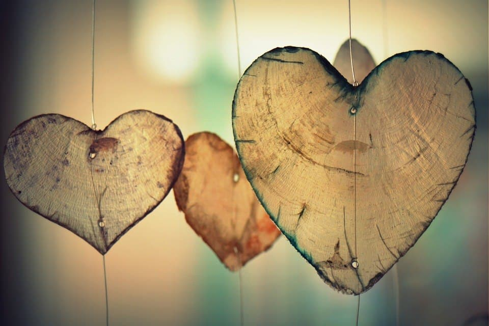 Wooden-crafted hearts symbolizing using one's heart to unlock potential.