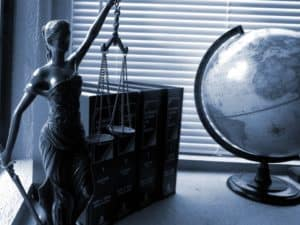 A statue of justice holding a sword and scales, books, and a globe sit on a desk.