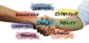 Two people shake hands. Above the image concepts are displayed, including learning, experience, ability, growth, training, competence, knowledge, and skills.