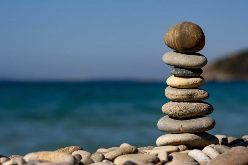 Several rocks are stacked on top of one another next to the beach.