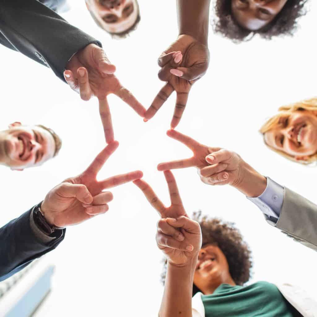 5 employees at a nonprofit link their fingers together to form the outline of a star.