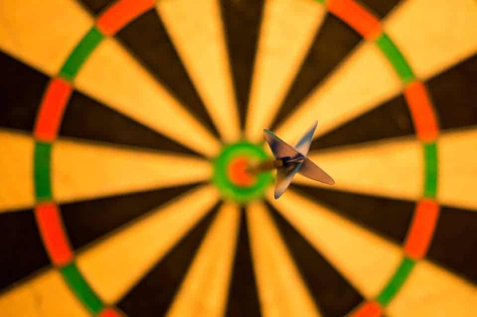 Pictured: A dart hitting bullseye on a dart board. This represents making new business resolutions targets.