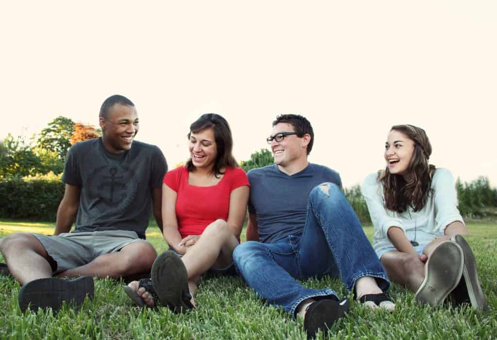 Pictured: Different people sitting on grass. They can be addressed using different pronouns depending on their sex.