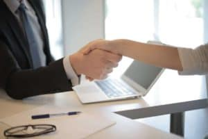 Pictured: A hiring manager shaking hands with a future employee. This represents the importance of hiring strategies.