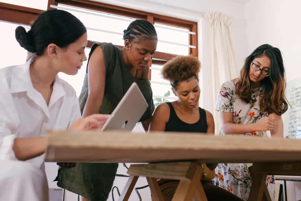 Four women collaborate on a project.