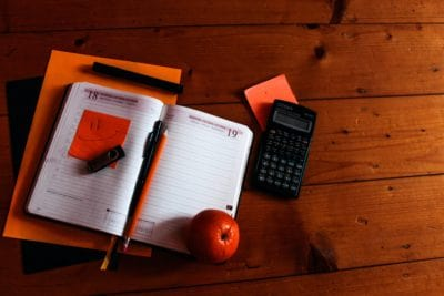 A calendar with a sticky note, calculator, and pens sit on a desk.
