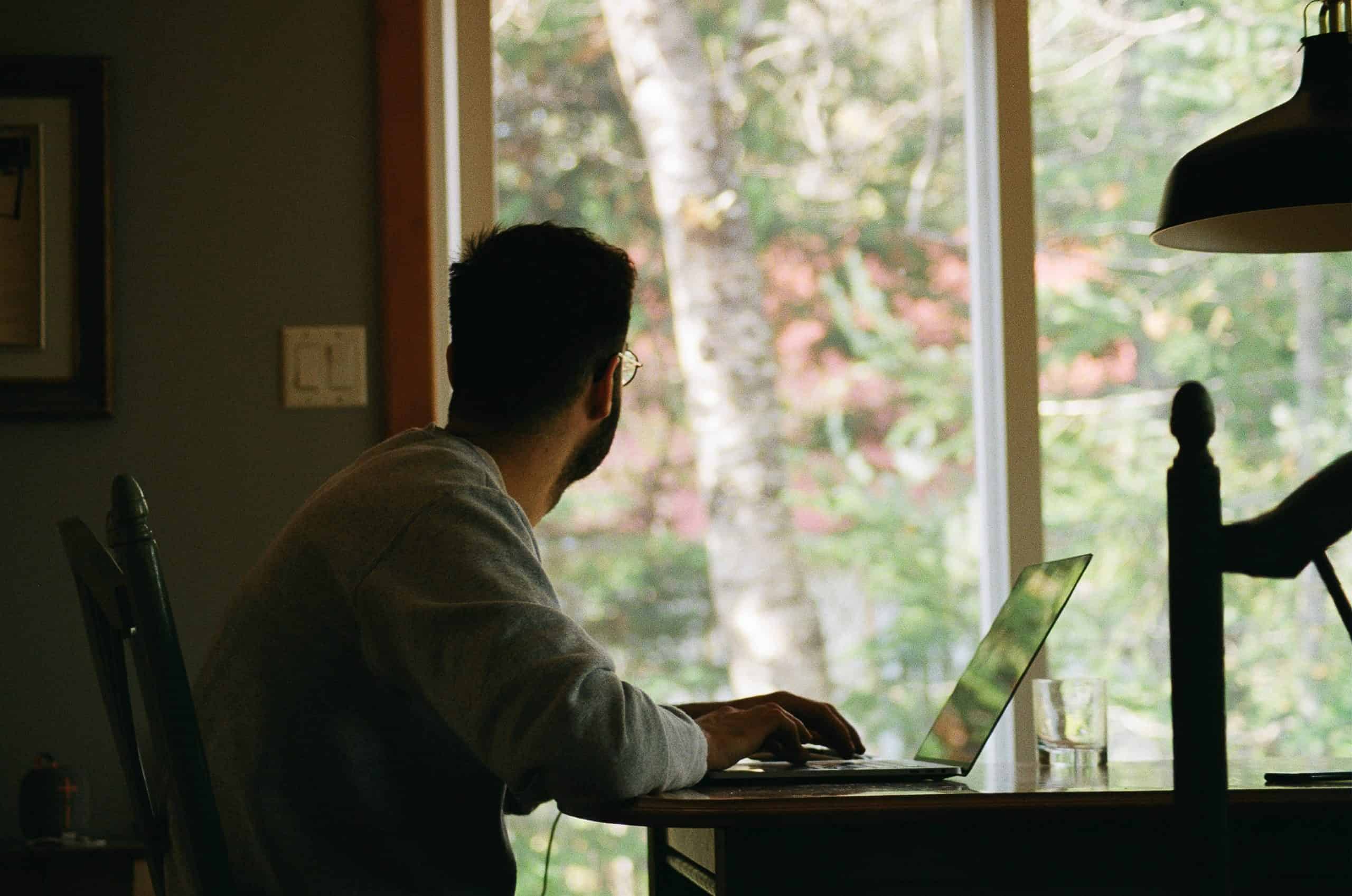 man looking out window while working